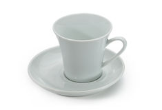 Vit keramisk kaffekopp och vitt keramiskt tefat Arkivbild