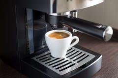 Vit keramisk kopp av espresso med kaffemaskinen Arkivfoto