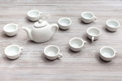 Vit keramisk koppar och tekanna på grå färgbrunttabellen Arkivbilder