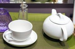 Vit keramisk tekanna och kopp på en grön servett fotografering för bildbyråer