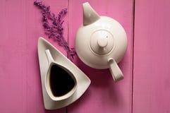 Vit keramisk tekanna och kopp te för tappning på en glamorös bakgrund royaltyfria foton