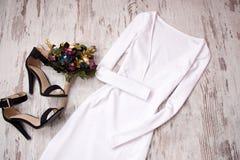 Vit klänning med en muff, skor, bukett spelrum med lampa Trendigt begrepp, bästa sikt Royaltyfria Foton