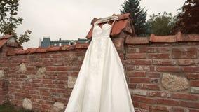 Vit klänning på tegelstenväggen stock video