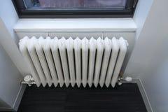 Vit klassisk vattenvärmeapparat för gammal skola vid fönstret av kontoret eller hemmet royaltyfria bilder