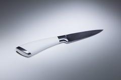 Vit kniv på en tabell Arkivbild