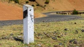 Vit kolonn för konkret väg med det svarta diagonala bandet som blir på sidan av den slingrande vägen med stenar Arkivbilder