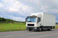 Vit kommersiell leveranslastbil på vägen Arkivfoto