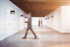 Vit kontorshögskolakorridor, rader av dörrar, man Arkivfoton