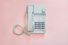 Vit kontorstelefon på rosa bakgrund Arkivbilder