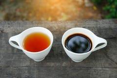 Vit kopp av grått te och kaffe för greve på träbakgrund Fotografering för Bildbyråer