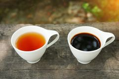 Vit kopp av grått te och kaffe för greve på träbakgrund Royaltyfri Foto