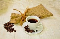 Vit kopp av svart kaffe med säckvävsäcken av grillade kaffebönor på den vita linnetabell-torkduken Royaltyfri Foto