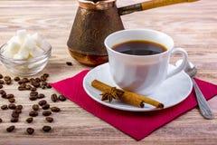 Vit kopp av svart varmt kaffe på tefatet som tjänas som med kaffebönor, kuber för vitt socker i en bunke, stic teskeden, anis och arkivfoto