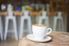 Vit kopp av varmt ånga kaffe på en gammal inloggning kafét med den suddiga cafeterian Royaltyfri Bild
