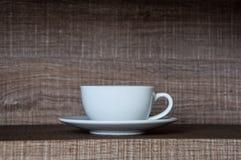 Vit kopp för kaffe med det vita tefatet på Blurred den bruna trähyllan fotografering för bildbyråer