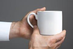 Vit kopp i händer arkivfoto