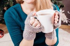 Vit kopp i händerna av en flicka Royaltyfri Foto