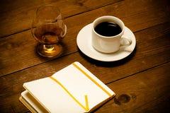Vit kopp kaffe, konjak i ett exponeringsglas och anteckningsbok på gammal woode Arkivbild
