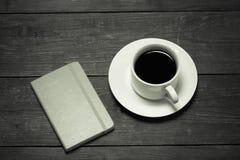 Vit kopp kaffe och anteckningsbok på den gamla trätabellen tonat Fotografering för Bildbyråer