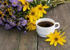 Vit kopp kaffe och bukett av blommor Royaltyfria Foton