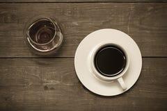 Vit kopp kaffe och konjak i ett exponeringsglas på den gamla trätabellen T Royaltyfria Bilder