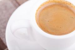 Vit kopp kaffe på bordduk Royaltyfria Foton