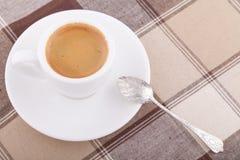 Vit kopp kaffe på bordduk Arkivfoto