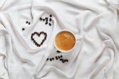 Vit kopp kaffe på ett siden- tyg Spridda kaffebönor i form av en hjärta Romantisk frukost för valentin dag Royaltyfri Fotografi