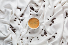 Vit kopp kaffe på ett vitt siden- tyg Espressokaffekopp Spridda kaffebönor på ett vitt siden- tyg Royaltyfri Fotografi