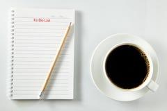 Vit kopp kaffemorgon på trätabellen med anteckningsboken Royaltyfri Foto