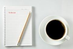 Vit kopp kaffemorgon på trätabellen med anteckningsboken Royaltyfri Bild