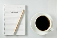 Vit kopp kaffemorgon på trätabellen med anteckningsboken Arkivfoton