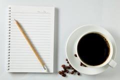 Vit kopp kaffemorgon på trätabellen med anteckningsboken Fotografering för Bildbyråer