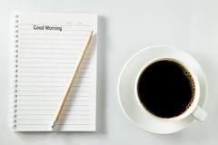 Vit kopp kaffemorgon på trätabellen med anteckningsboken Royaltyfria Foton