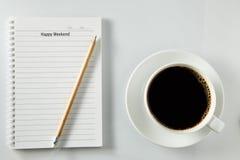 Vit kopp kaffemorgon på trätabellen med anteckningsboken Arkivbilder