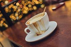 Vit kopp med driftigt aromkaffe på en tabell royaltyfri foto