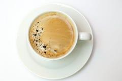 Vit kopp med espressokaffe som isoleras på vit Arkivfoto