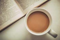 Vit kopp med kaffe bredvid en öppen bok arkivbild