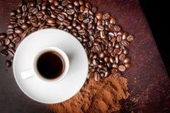 Vit kopp med kaffe nära kaffebönor och kaffepulver Royaltyfri Foto