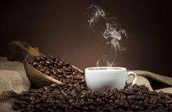 Vit kopp med kaffebönor på mörk bakgrund Arkivbild