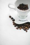 Vit kopp med korn av kaffe och sauceren Arkivbild