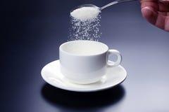 Vit kopp med skeden med socker Fotografering för Bildbyråer