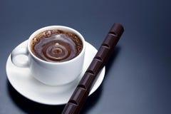 Vit kopp med svart kaffe och choklad på tefatet Royaltyfri Bild