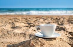 Vit kopp med te eller kaffe på sandstrandframdel av havet Arkivfoto