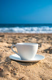 Vit kopp med te eller kaffe på sandstrandframdel av havet Fotografering för Bildbyråer