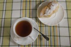 Vit kopp med te och bakelse på en platta Royaltyfri Fotografi