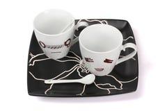 Vit kopp och svart platta Royaltyfria Bilder