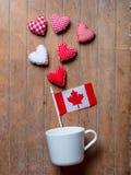 Vit kopp på att ligga på sida med Kanada flagga- och hjärtaformer arkivbilder