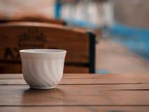 Vit kopp på den wood tabellen Arkivfoto