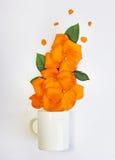 Vit kopp som är full av gulingroskronblad Arkivfoto